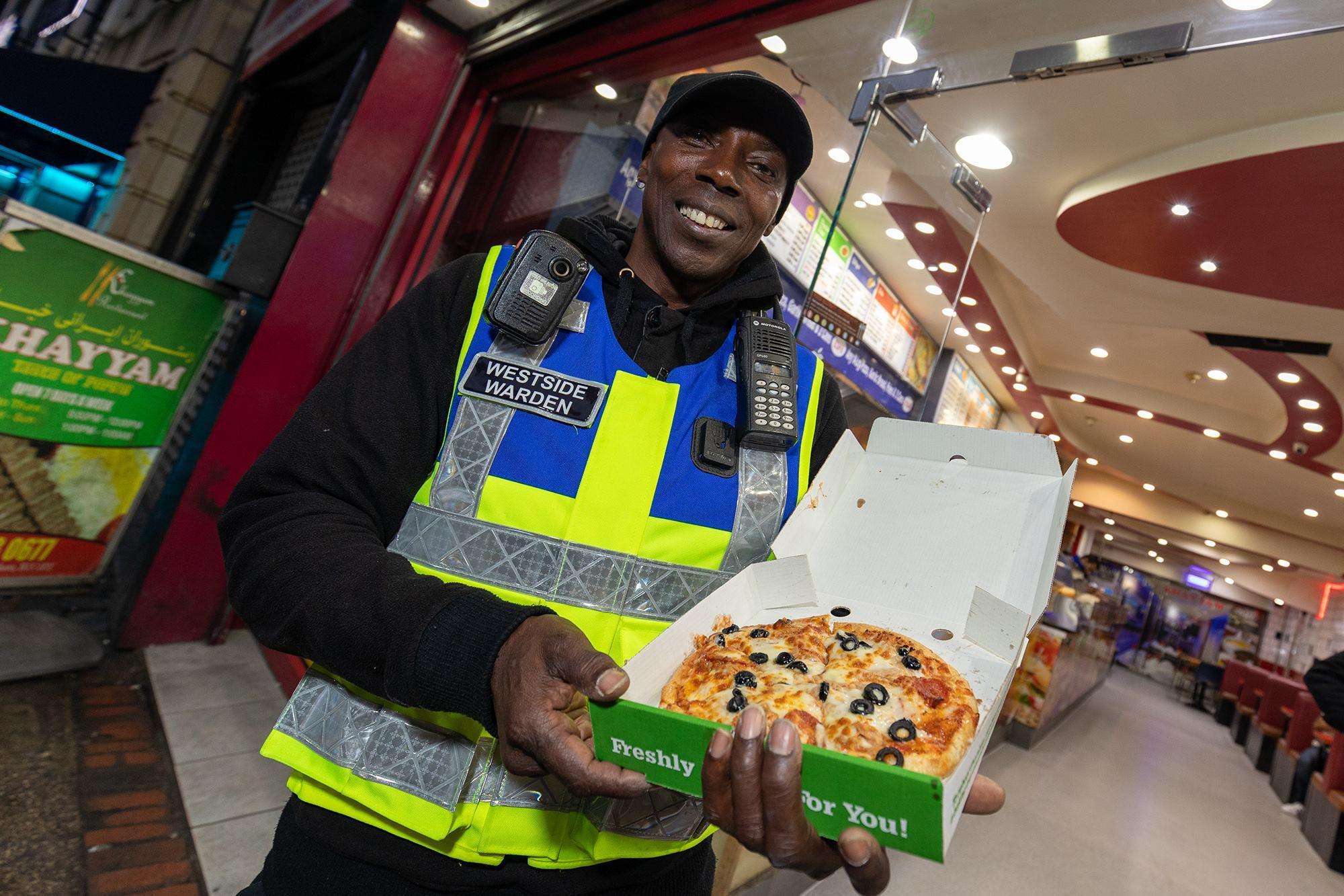 Street warden Enoch White holding pizza outside Pit Stop takeaway